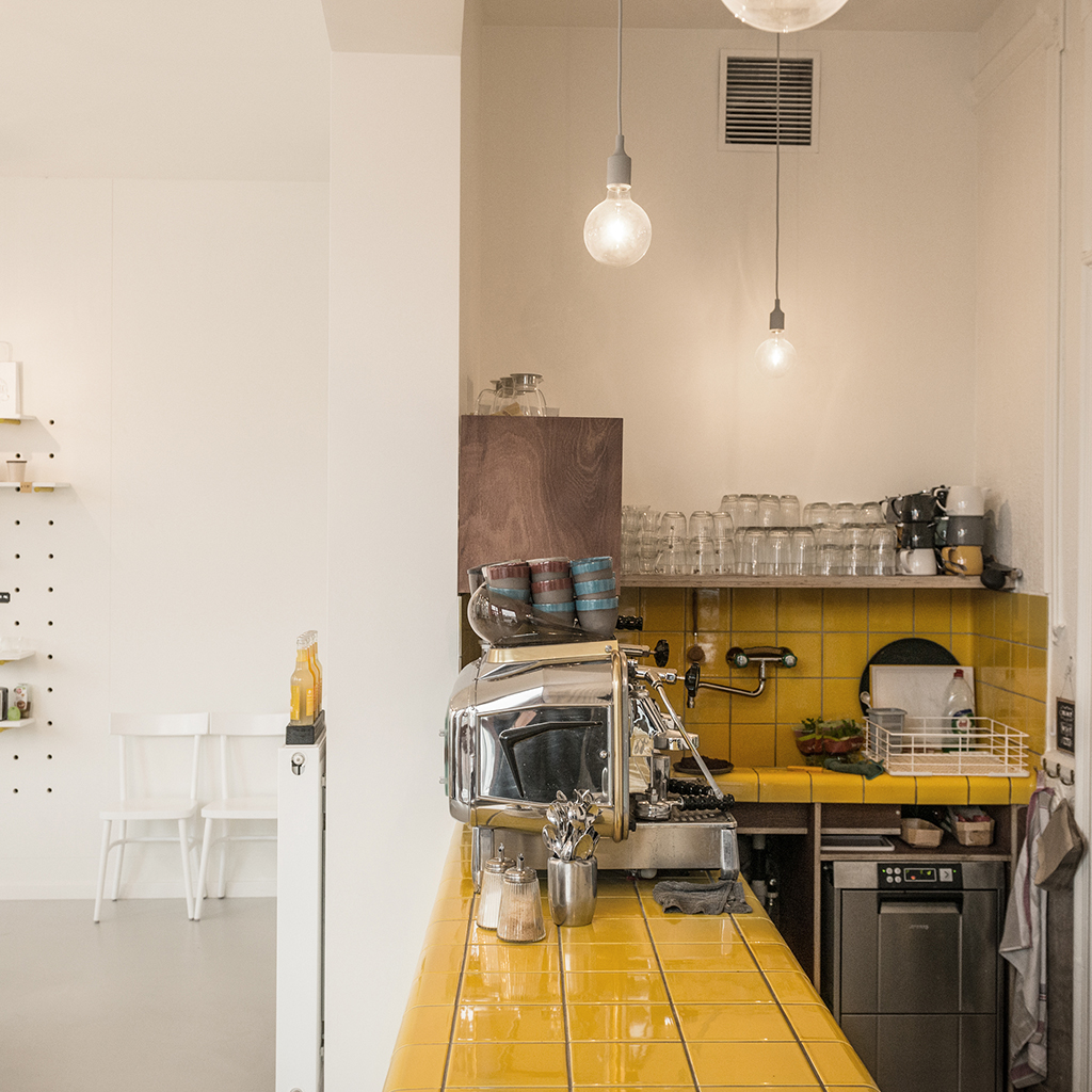 cafe with yellow rounded 3d tiles with integrated ventilation, drain, shelves and sink, belgium