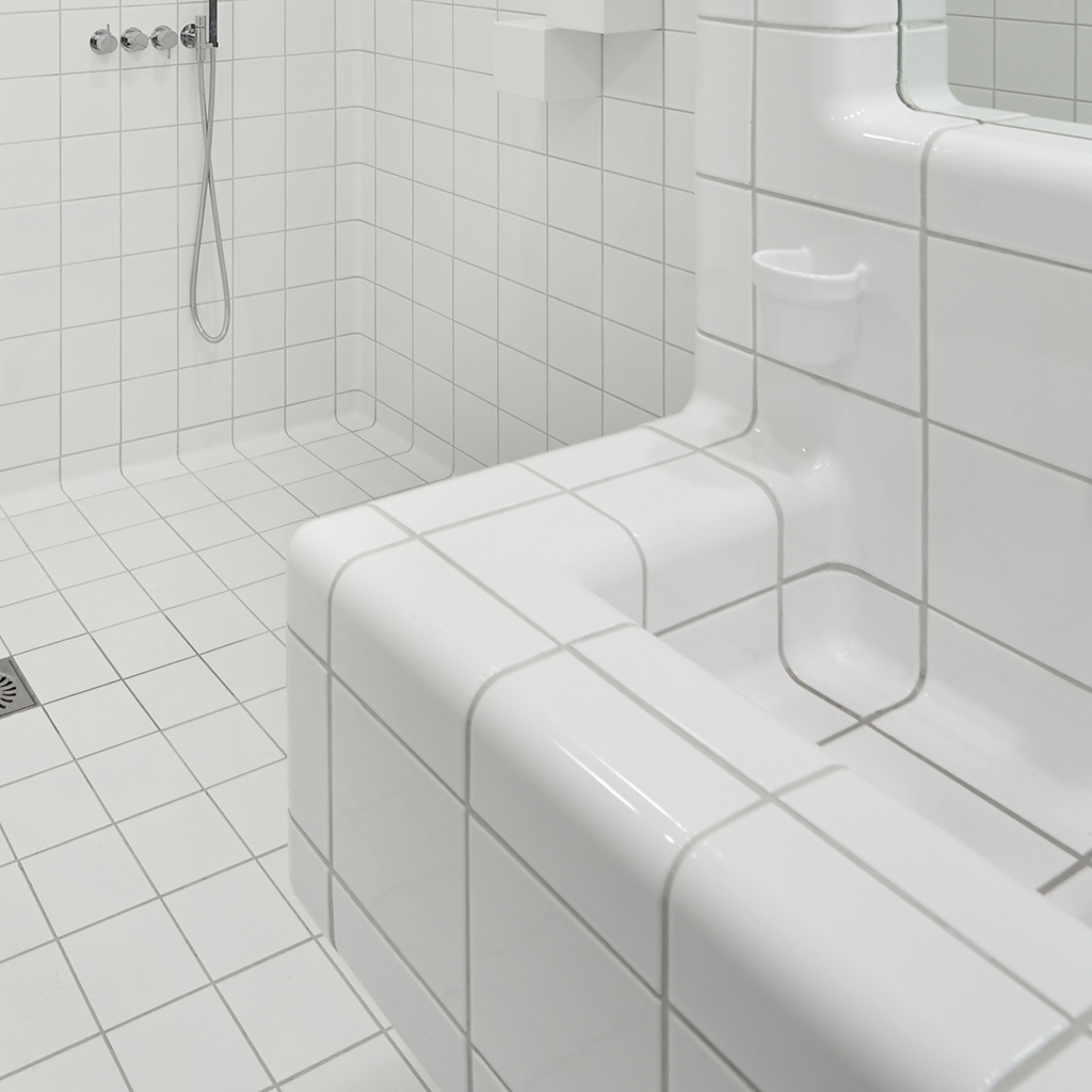 rounded white tiles in shower, three-dimensional construction and functional tiles like cupholder