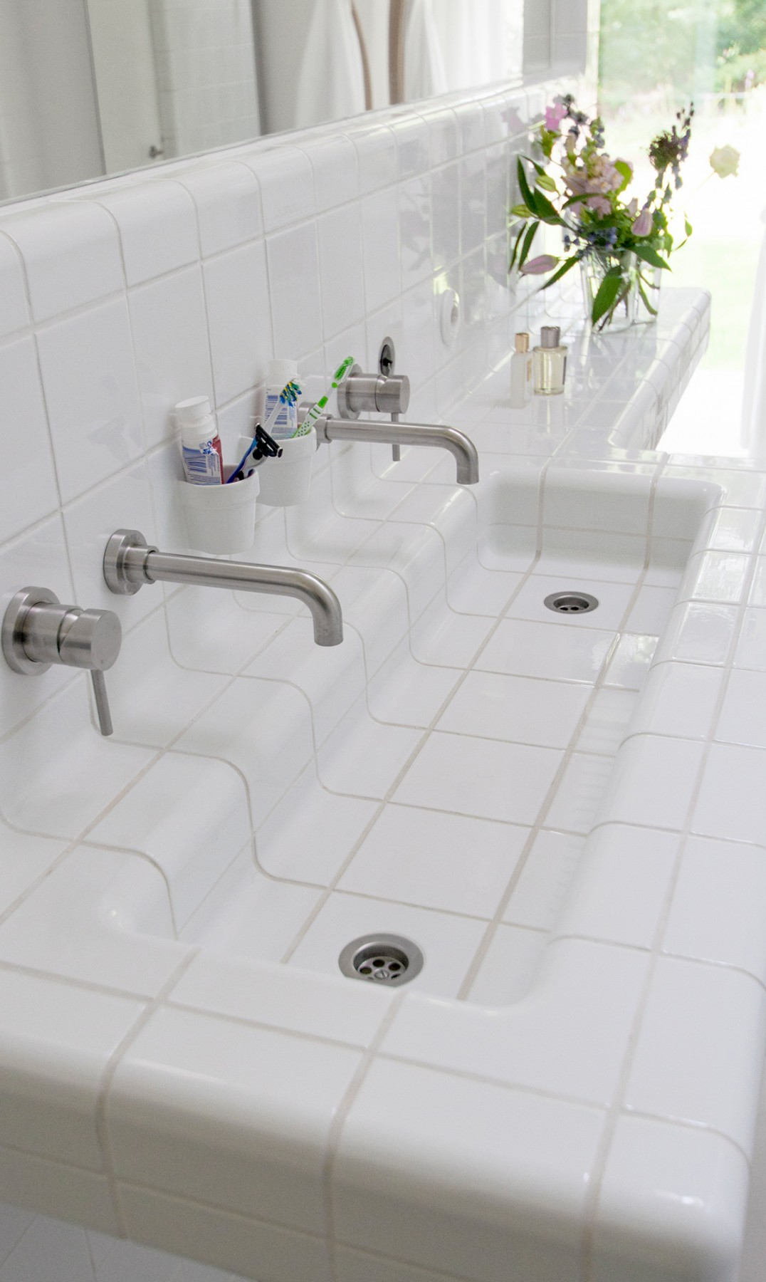 rounded white tiles in sink, three-dimensional construction and functional tiles like cupholder and taps